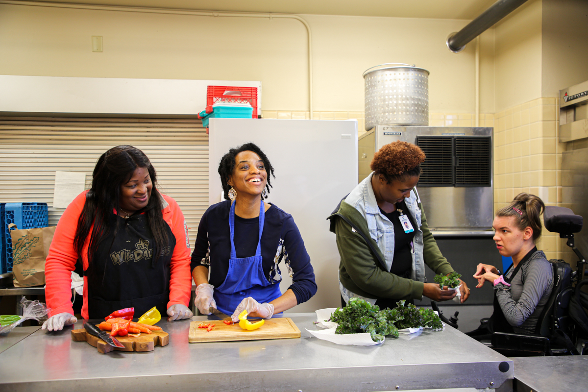 Guild members and employees cook in the kitchen